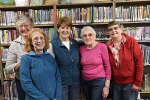 Five smiling women posing in front of a bookcase