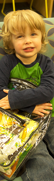 Child holding raising reader backpack smiling at the viewer.