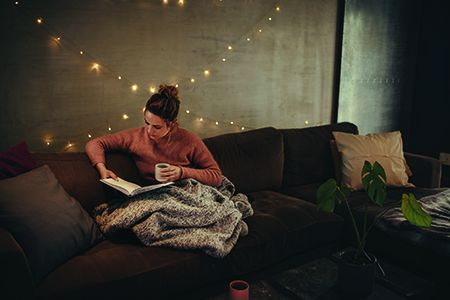 A woman sits on a sofa, reading a book under a blanket in a comfy looking room.