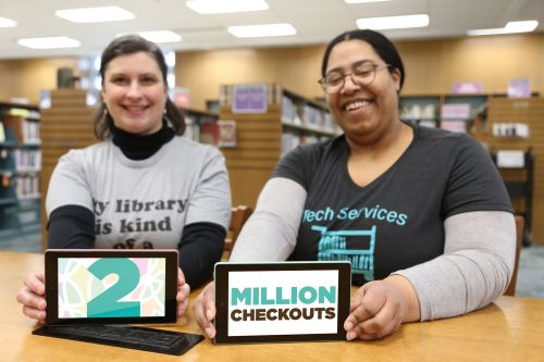 Thais (left) and Jessica (right) sit at a desk and each hold a Kindle eReader with the words 2 Million Checkouts on the screen.