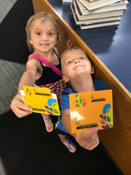 Two young blonde children hold library cards