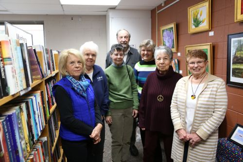 7 members of the Haslett friends pose in the Bookend used book store