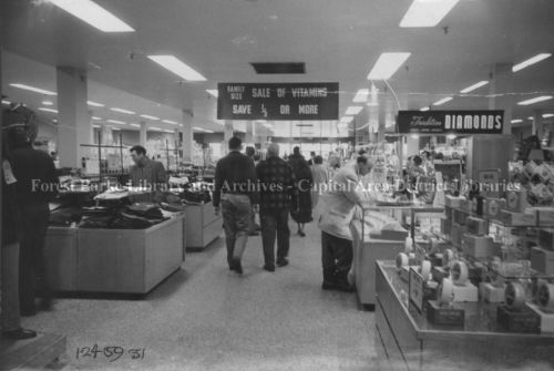 Black and white photograph of interior of department store. Shoppers browsing displays.
