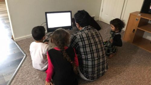Refugee family uses computer donated by library.