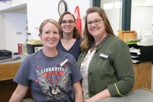 CADL Williamston staff members Micki, Caitlinn and Julie stand behind a circ desk in the new library